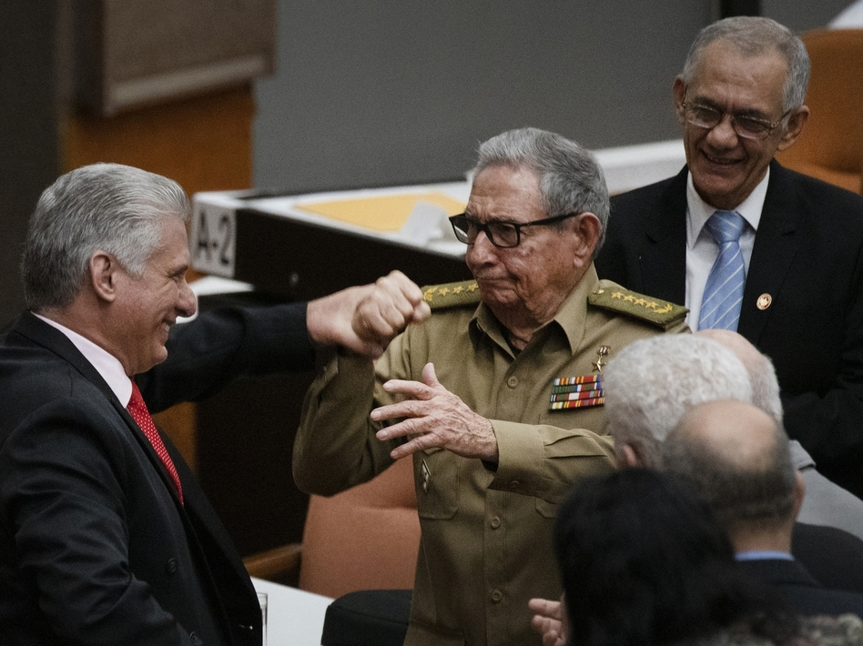 Raúl Castro, first secretary of the Cuban Communist Party and the country's former president, clasps hands with Cuban President Miguel Mario Díaz-Canel Bermúdez during the closing session at the National Assembly of Popular Power in 2019 in Havana. (Ramon Espinosa/AP)
