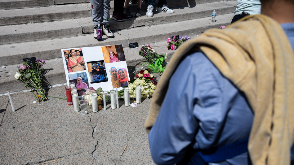 A woman views a collage of photos of Amarjeet Johal during a vigil at Monument Circle on Sunday in Indianapolis. Four of the people killed in the mass shooting were members of the Sikh community. (Jon Cherry/Getty Images)