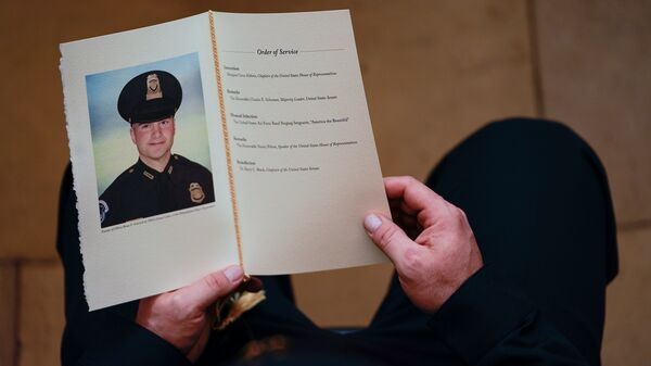 A U.S. Capitol Police officer holds a program as Brian Sicknick lays in honor in the Capitol Rotunda on Feb. 3. A medical examiner has determined that Officer Sicknick died of natural causes following the Jan. 6 insurrection.