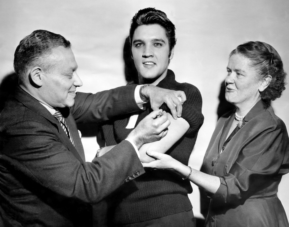 Elvis Presley got his polio vaccination from Dr. Harold Fuerst and Dr. Leona Baumgartner at CBS' Studio 50 in New York City on Oct. 28, 1956. The chart-topping singer took part in a March of Dimes campaign to convince teens to get vaccinated. (Seymour Wally/NY Daily News Archive via Getty Images)
