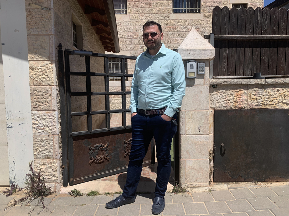 Yehuda Ben Sheetrit, an ultra-Orthodox Jewish Israeli, lost his wife, Osnat, to COVID-19. He stands outside the new apartment he has moved into with his four children after losing his wife.