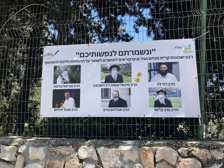 A poster in Jerusalem features rabbis who call on residents to get vaccinated against COVID-19.