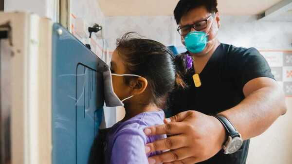A young girl waits as her chest X-ray is taken in a TB Móvil van clinic in Lima, Peru.