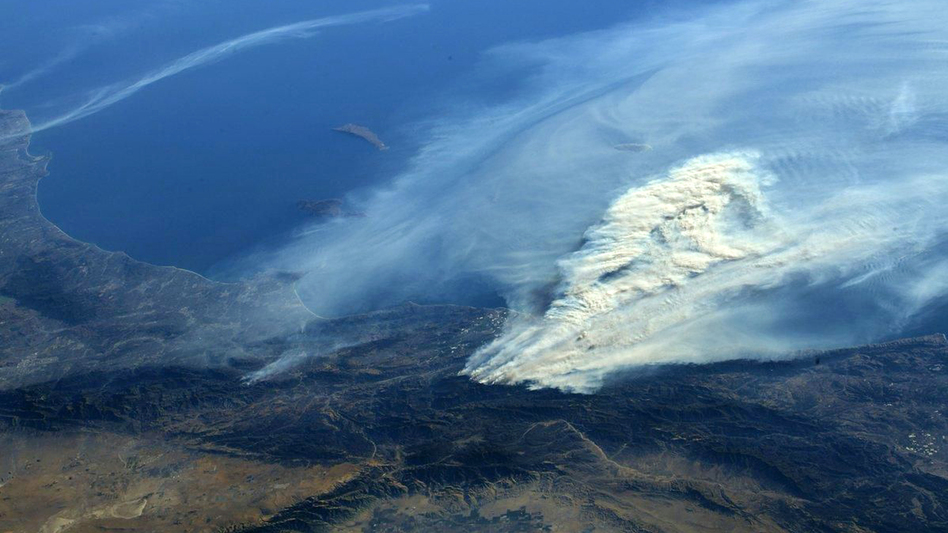 This 2017 photo from the International Space Station shows smoke from wildfires in Ventura County, Calif. The increasing human and economic toll of extreme weather events will underscore the urgency of President Biden's message at a global summit focused on reducing carbon emissions.