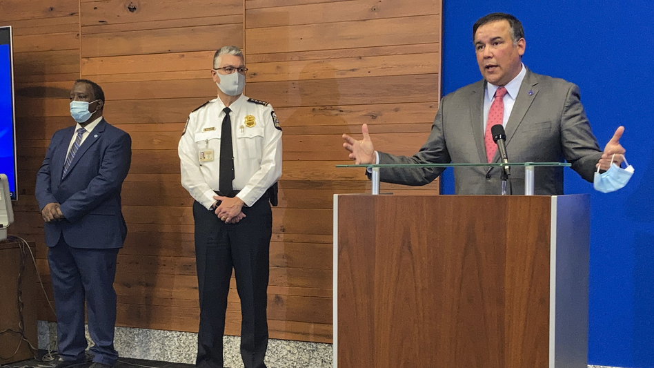 Columbus, Ohio, Mayor Andrew Ginther speaks during a news conference Wednesday about the fatal police shooting of 16-year-old Ma'Khia Bryant on Tuesday. Columbus Public Safety Director Ned Pettus (left) and interim Police Chief Michael Woods listen. (Andrew Welsh-Huggins/AP)