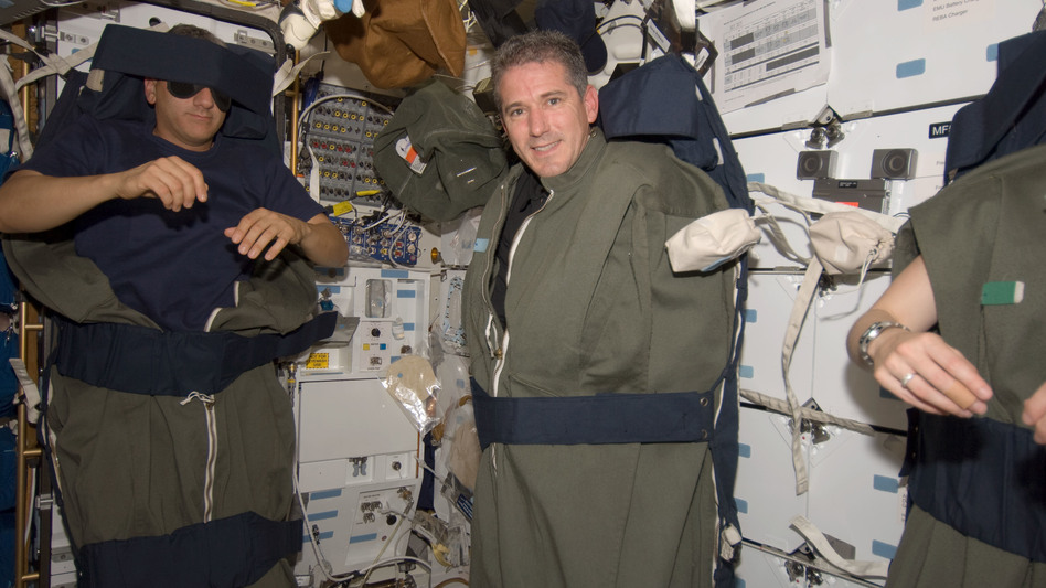 Astronauts Mike Massimino (left) and Michael Good are pictured in their sleeping bags, which are attached to the lockers of the Earth-orbiting space shuttle Atlantis in 2009.