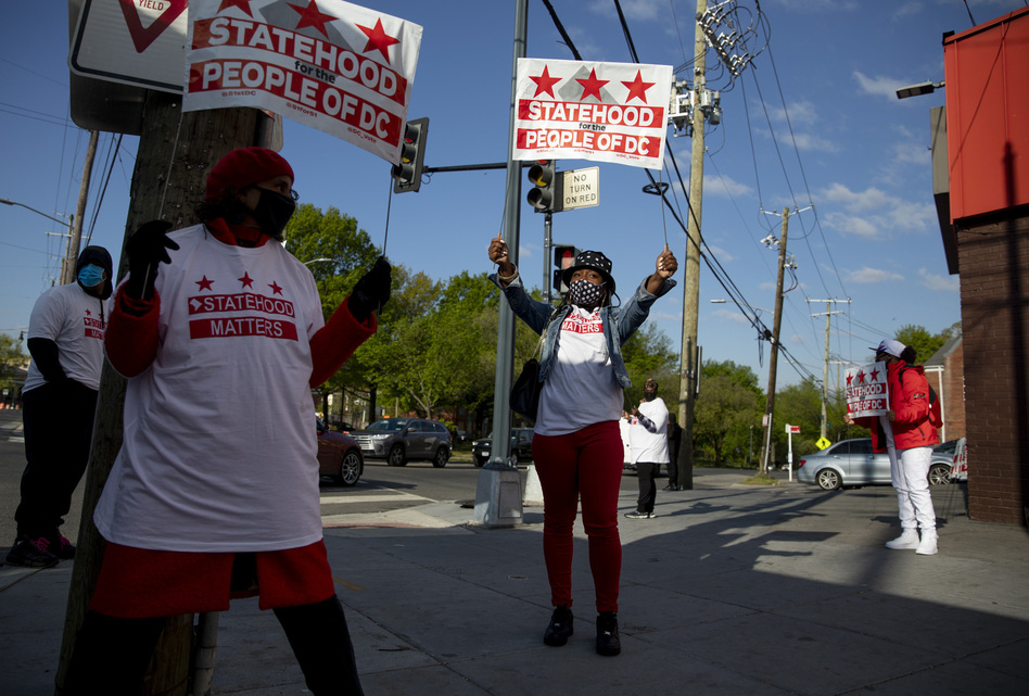 Supporters stand at the corner of Martin Luther King Jr. Ave & Malcolm X Ave SE in Ward 8 in Washington, D.C.