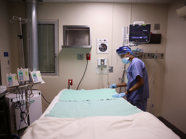 Intensive Care Unit nurse Subramanya Kirugulige prepares a bed for an arriving COVID-19 patient at Roseland Community Hospital in Chicago in December. A large study has found that people with severe initial cases of COVID-19 tend to be at greater risk of more health problems later on.