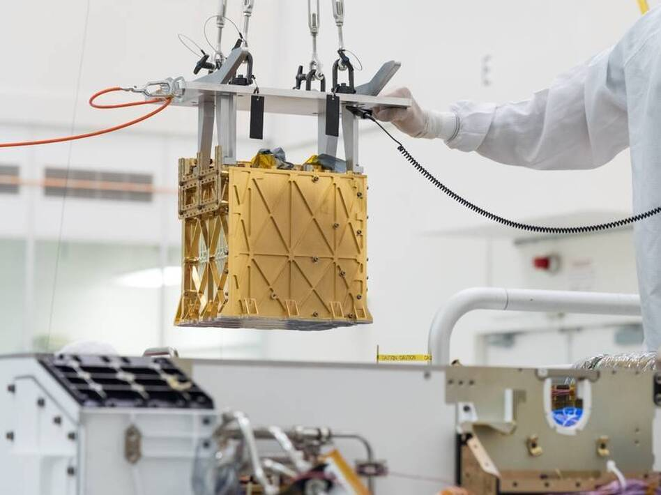Technicians at NASA's Jet Propulsion Laboratory lower an instrument known as MOXIE, or the Mars Oxygen In-Situ Resource Utilization Experiment, into the belly of the Perseverance rover. NASA announced the instrument had produced oxygen from the Martian atmosphere. (NASA/Jet Propulsion Laboratory-Caltech)
