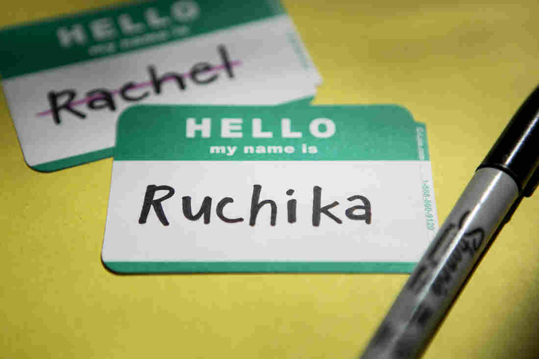 "A name tag that reads ""Hello my name is Ruchika"" sits on a yellow background with a permanent marker next to it. Behind and to the left of the name tag, is another name tag that reads ""Hello my name is Rachel"" with ""Rachel"" crossed out."