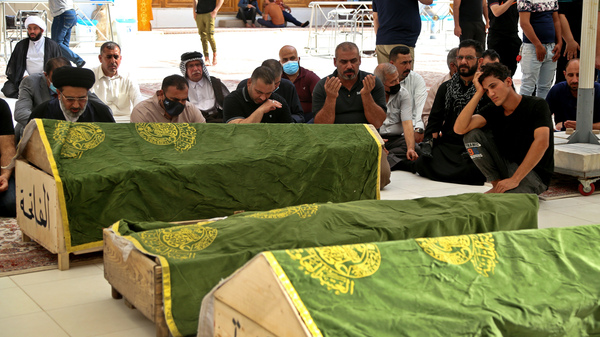 Mourners at the Imam Ali shrine in Najaf, Iraq, pray Sunday near the coffins of coronavirus patients who were killed in a hospital fire in Baghdad.