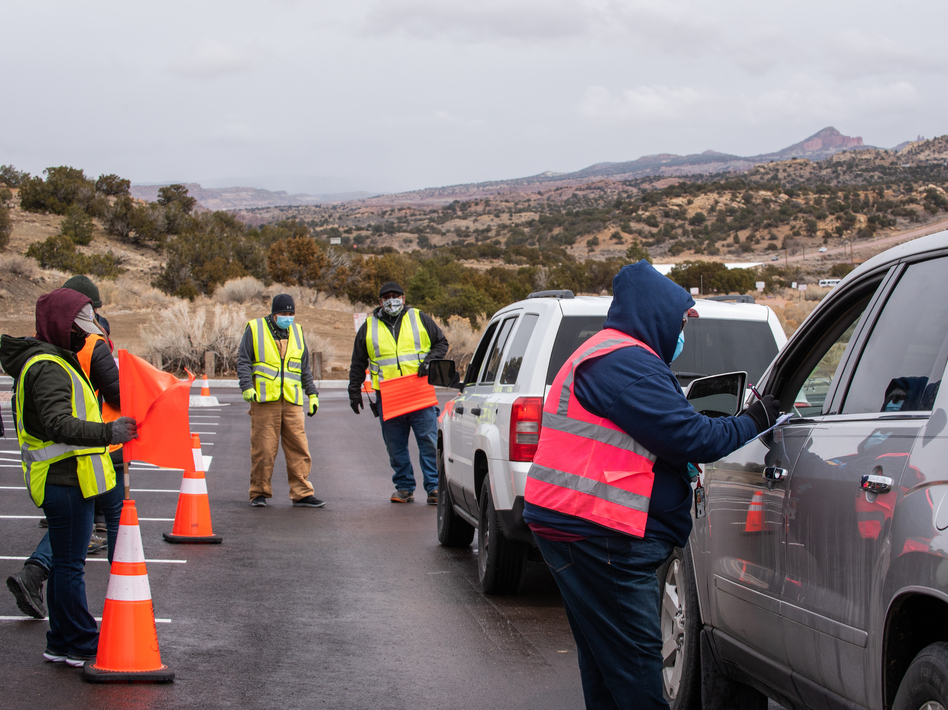 Workers greet arrivals at a drive-in vaccination site at University of New Mexico's Gallup campus in Gallup, N.M., on March 23. The Navajo Nation has vaccinated more than half of its adult population, outpacing the U.S. national rate. (Cate Dingley/Bloomberg via Getty Images)