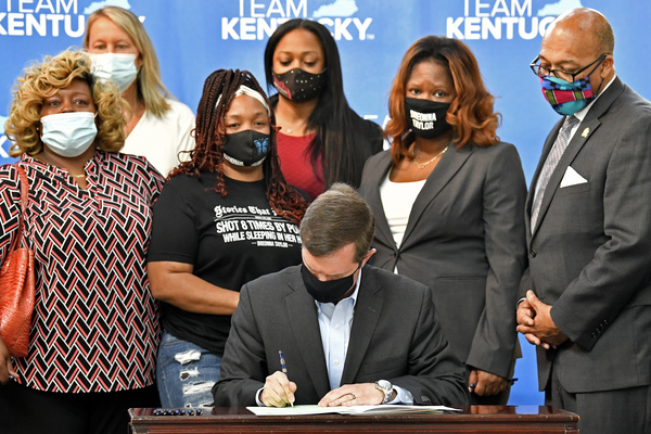 Kentucky Gov. Andy Beshear signs a bill enacting a partial ban on no-knock warrants, as Breonna Taylor's mother, Tamika Palmer, stands to his right.