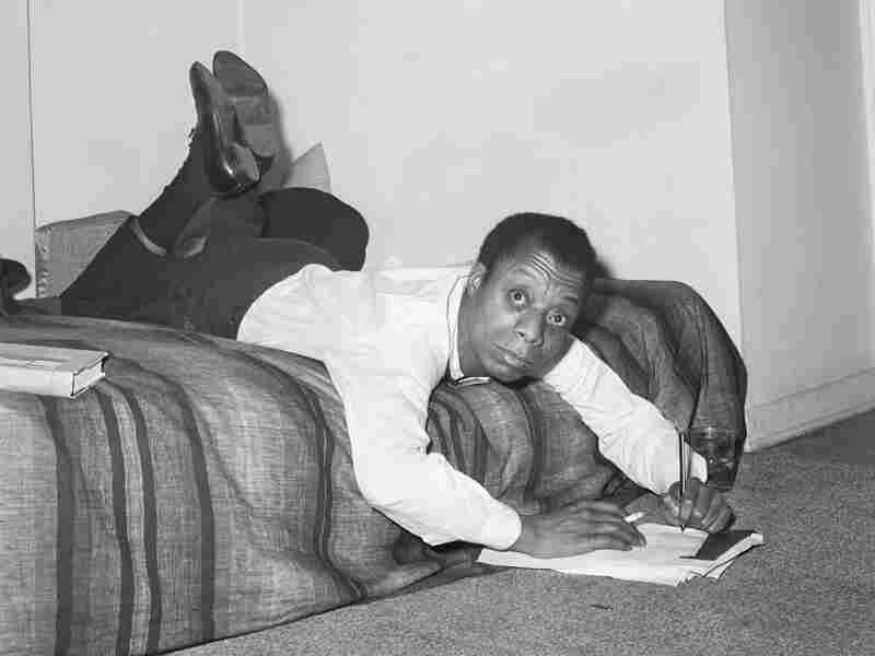 James Baldwin sprawls across his bed in his New York apartment to jot some notes down.