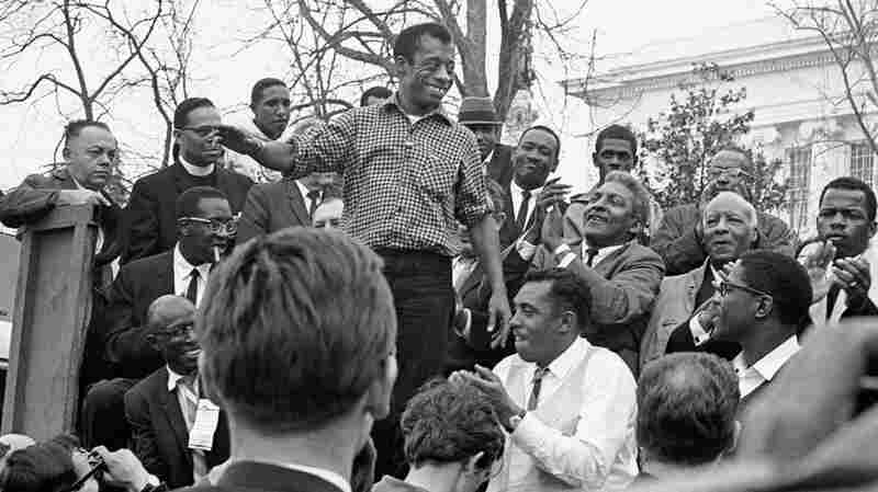James Baldwin smiles while addressing the crowd from the speaker's platform, after participating in the march from Selma to Montgomery in support of voting rights, March 1965.