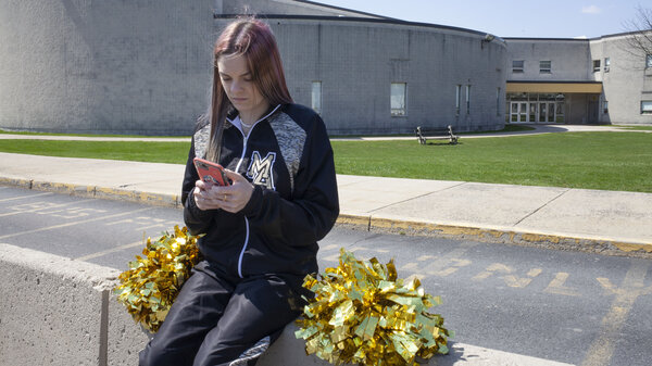 Brandi Levy wears her former cheerleading outfit as she looks at her mobile phone while sitting outside Mahanoy Area High School in Mahanoy City, Pa., on April 4.