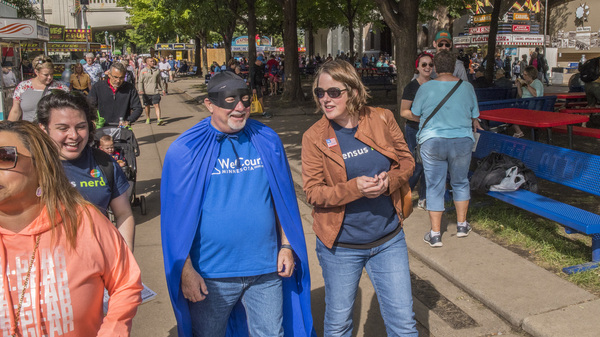 """Minnesota's state demographer, Susan Brower (center), walks with Dean Goldberg, donning a blue cape and black mask as """"Census Man,"""" through the 2019 Minnesota State Fair in St. Paul, Minn., to encourage residents to participate in the national head count."""
