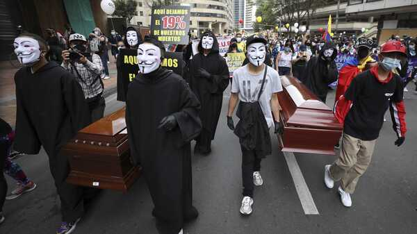 Protesters wearing Guy Fawkes masks carry empty coffins during a national strike to protest a government-proposed tax reform, in Bogotá, Colombia, on Wednesday.