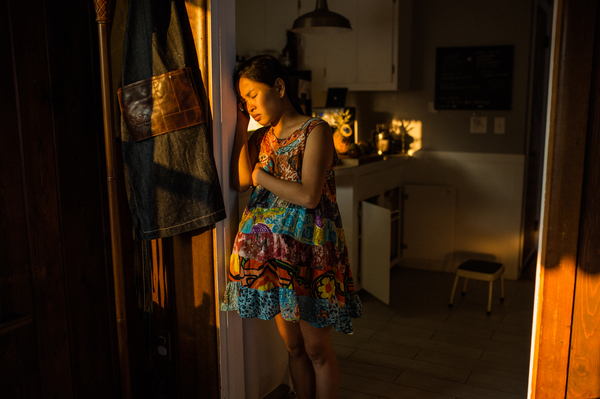 Cham Junglas, 29, rests her head against the door as she works through her labor pains for the home birth of her second child, Theodore. Junglas felt that the hospital experience of her first labor removed her from the intimate experience of birthing her child.