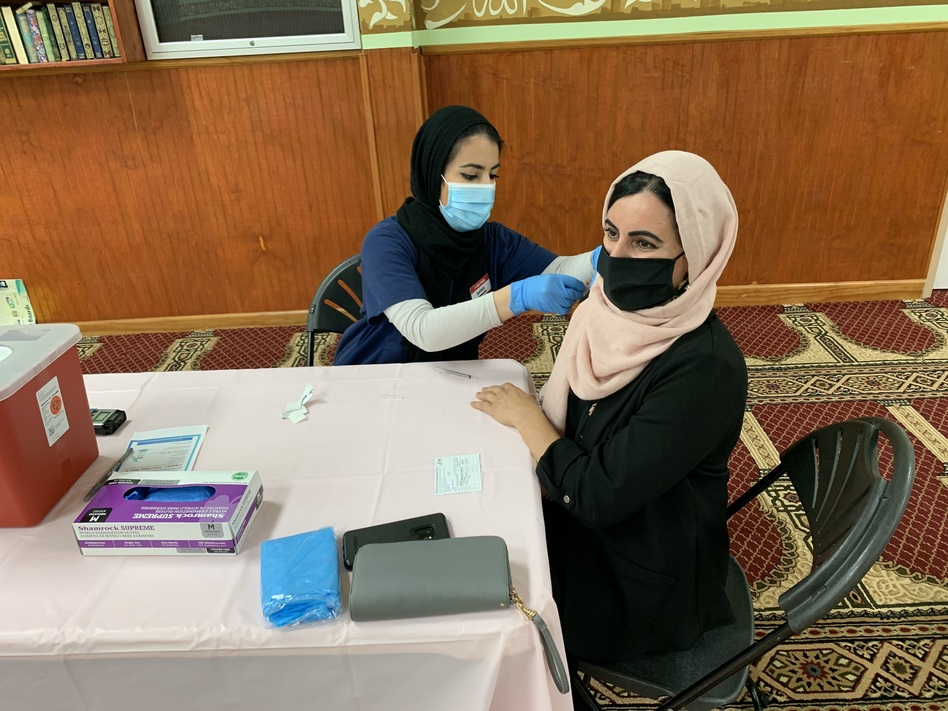 At the community center for Kurdish Americans in Nashville, Muhamed vaccinates her mother. The pre-med major, a trained pharmacy technician, spent weeks convincing her mother, who was in refugee camps as a child, that the vaccine is safe and effective.