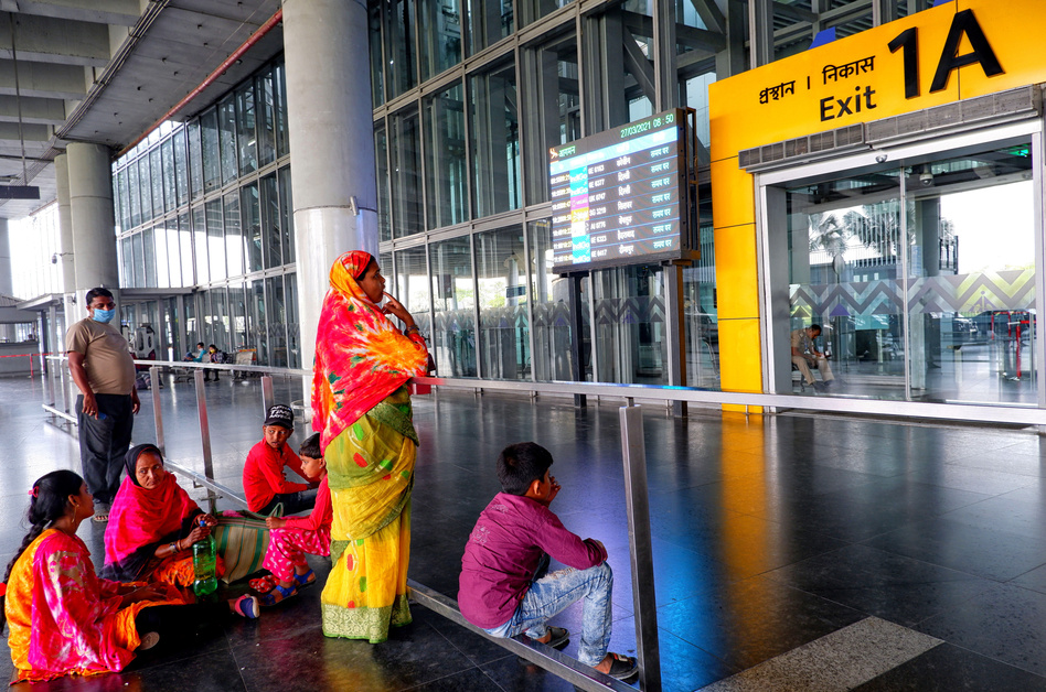 People wait at an exit gate at the Kolkata Airport Terminal. International air travel to and from India has been restricted as the country battles a catastrophic COVID-19 surge.