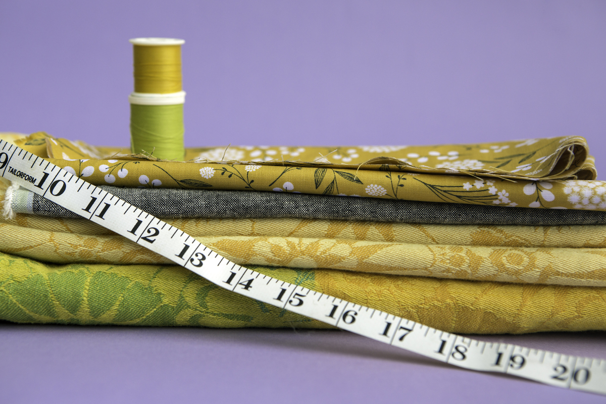 Three pieces of fabric in mustard yellow, dark gray, and bright yellow and green are stacked against a light purple backdrop. Two spools of thread in pea green and marigold yellow are stacked on top of the fabric, and a measuring tape is draped across the front.