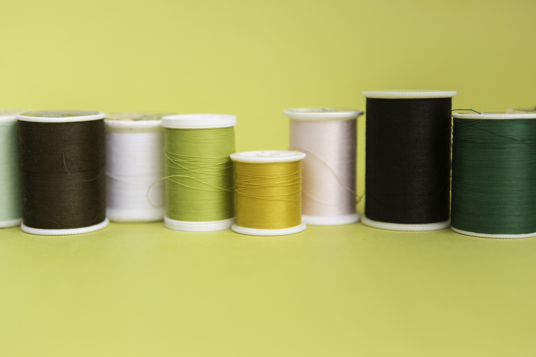 Spools of thread of varying colors are lined up in a loose row against a light yellow backdrop.