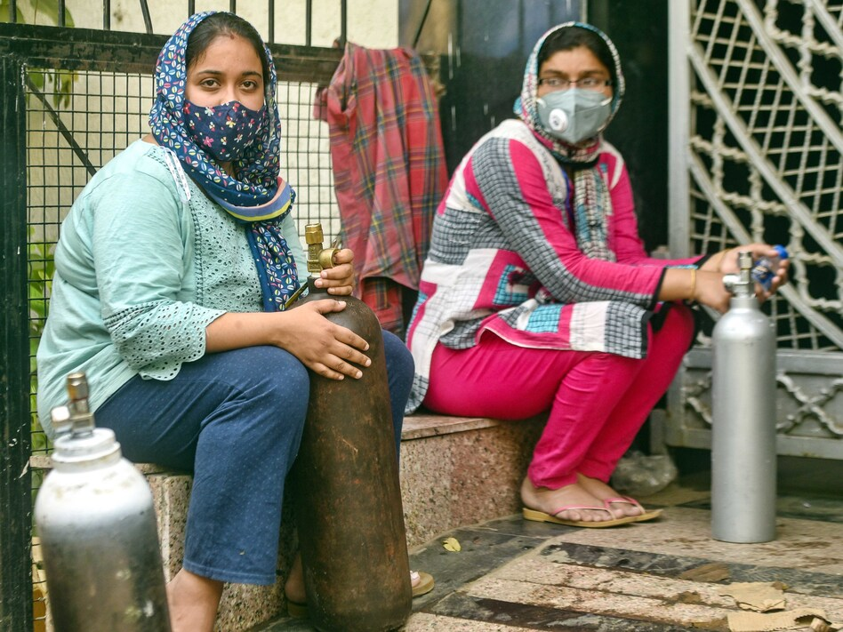 India has reported more than 20 million coronavirus cases, adding more than 2.6 million new cases in the past week alone. Here, women wait to refill empty oxygen cylinders in New Delhi. Oxygen shortages are blamed for deaths at even the best-equipped urban hospitals in India. (Amal KS/Hindustan Times via Getty Images)