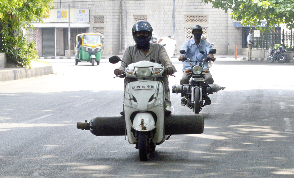 Scooter riders carry oxygen cylinders, hoping to find a source where they can refill the containers, in Bengaluru on May 1.