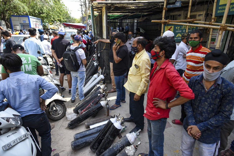 People wait to refill empty oxygen cylinders in New Delhi on May 3. Facing oxygen shortages, some hospitals are telling family members of patients to get their own oxygen.