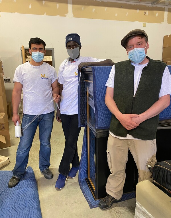 Anur Abdella (center), a refugee from Sudan, with colleagues at the moving company where he works in Connecticut. A multifaith team of local volunteers has helped Abdella, his wife and children get settled into their new life in the U.S.