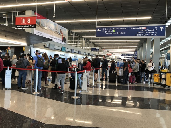 A line loops through security at Chicago's O'Hare International Airport as travelers return to the skies after mostly staying home during the coronavirus pandemic.