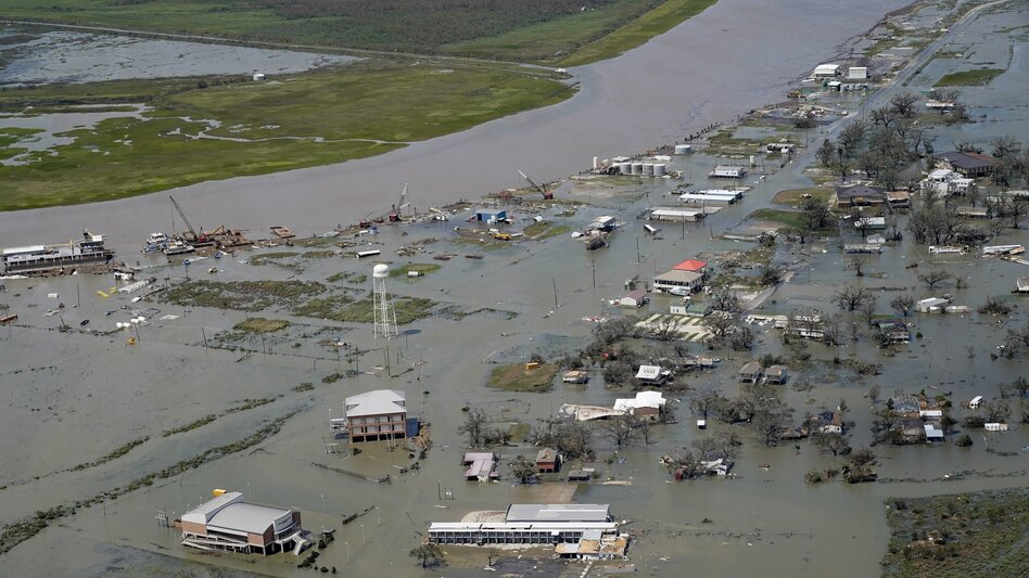 Buildings and homes are flooded in the aftermath of Hurricane Laura, on Aug. 27, 2020, in Cameron, La.  The warming climate is fueling more powerful storms, as well as intense rains and rising seas.