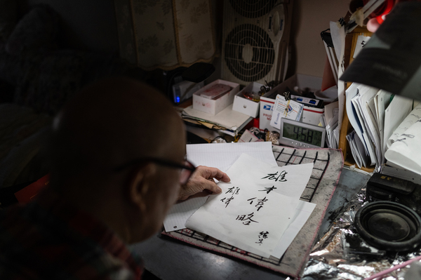 """Dock Lee, 90, adds his signature to a calligraphy script with the meaning of Eric Lee's name, """"majestic."""" Eric Lee's grandfather converted a corner of the home into a calligraphy writing set-up where he practices daily."""
