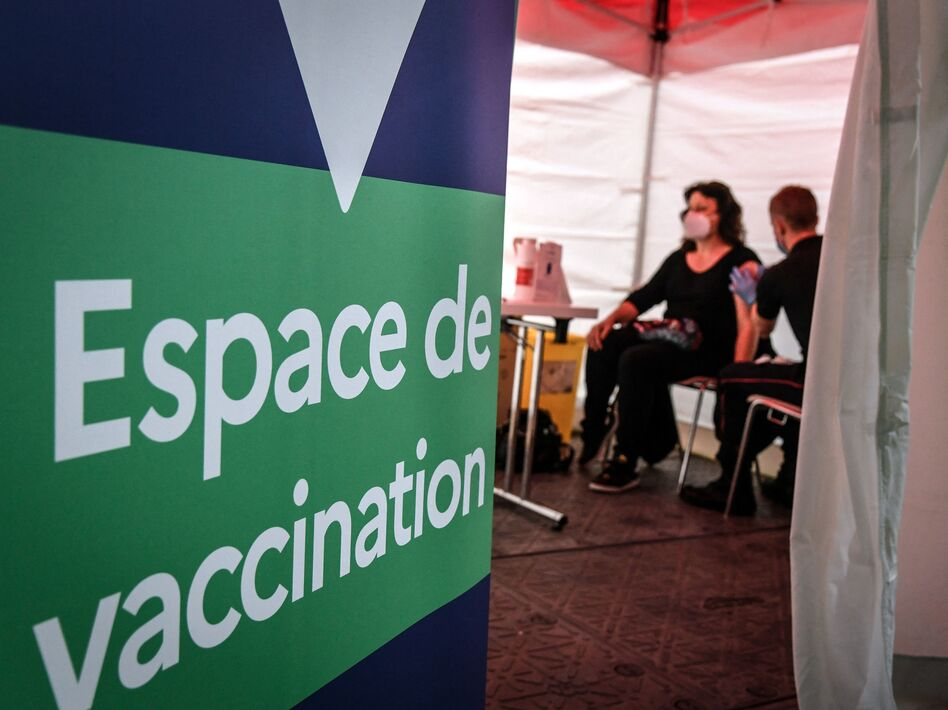 A firefighter administers the Pfizer-BioNTech COVID-19 vaccine at a vaccination center near Paris on Monday. The European Union has signed a deal to buy as many as 1.8 billion doses. (Bertrand Guay/AFP via Getty Images)