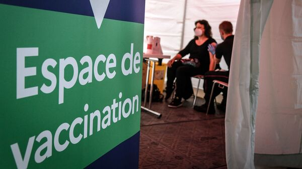 A firefighter administers the Pfizer-BioNTech COVID-19 vaccine at a vaccination center near Paris on Monday. The European Union has signed a deal to buy as many as 1.8 billion doses.