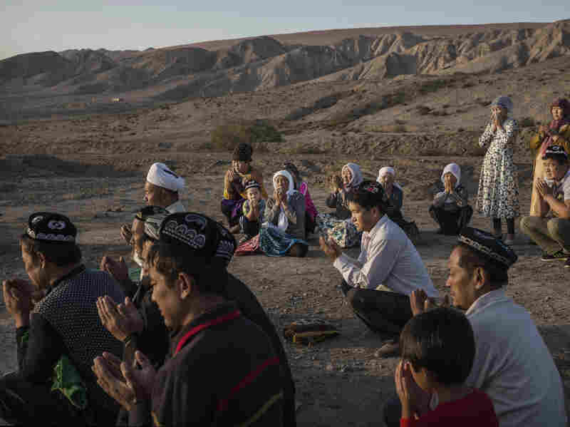 A Uyghur family pray at the grave of a loved one in the western Xinjiang province, China.The Corban festival, known to Muslims worldwide as Eid al-Adha or 'feast of the sacrifice', is celebrated by ethnic Uyghurs across Xinjiang. Ethnic Uyghurs have been subjected to restrictions on religious and cultural practices for decades by the China's Communist Party.