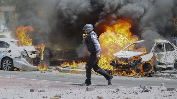 An Israeli firefighter walks next to cars hit by a rocket fired from Gaza on Tuesday in the southern Israeli city of Ashkelon.