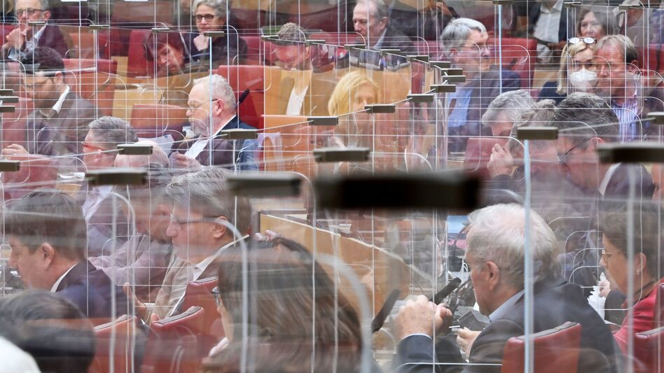"""Calling COVID-19 """"a terrible wake-up call,"""" an independent review panel says national and international leaders failed to respond adequately to the pandemic. Here, members of the Bavarian state Parliament sit among clear panels in Munich in October. (Peter Kneffel/POOL/AFP via Getty Images)"""