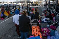 Migrants and asylum seekers are seen after spending the night in one of the car lanes off the San Ysidro Crossing Port on the Mexican side of the U.S.-Mexico border in Tijuana on April 24, 2021. A group of migrants asked U.S. migration authorities to allow them to start their migration process and decided to stay at the crossing port to pressure for a solution to their situation.
