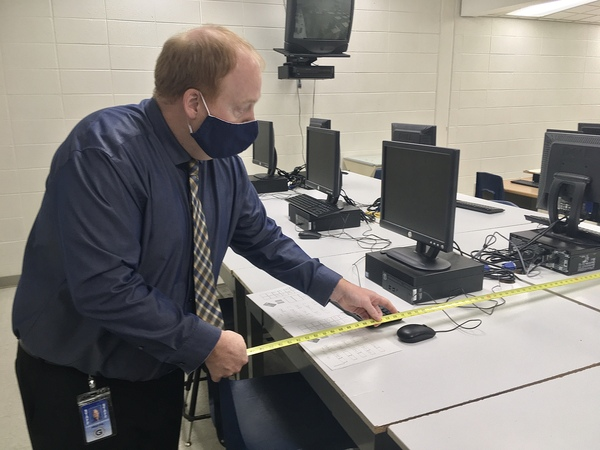 Gaylord High School principal Chris Hodges measures the space between seats in a yearbook class. A student in the class tested positive for covid, and Hodges is working with the local health department to trace people who might have been exposed to her at school.
