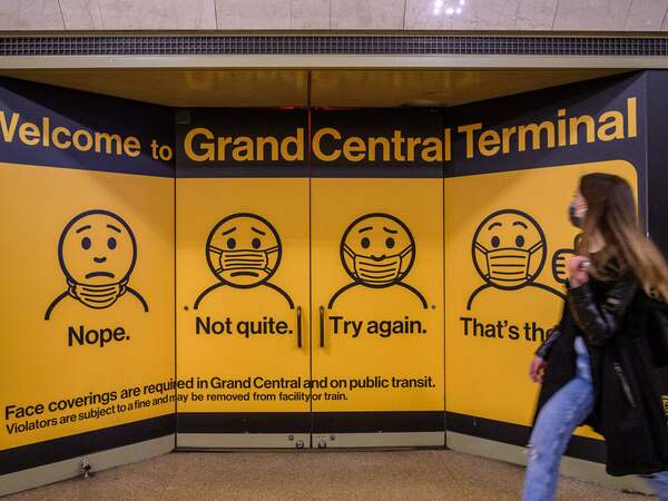 A woman walks past posters explaining mask requirements at Grand Central Terminal train station in New York City on Wednesday. Rules requiring masks on transit are unchanged by the Centers for Disease Control and Prevention's updated mask guidance for fully vaccinated people.