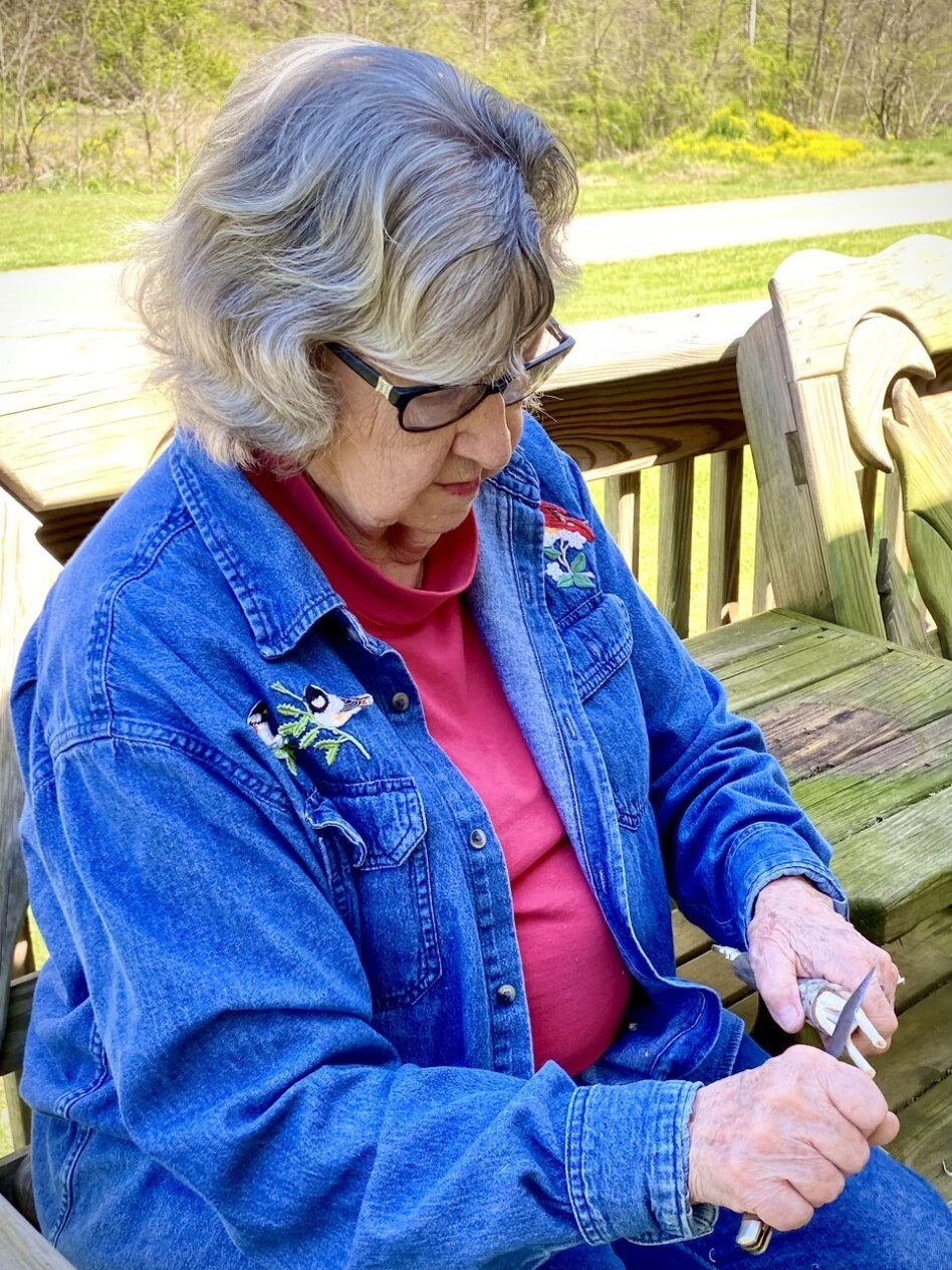 Minnie Adkins sits on her porch in rural eastern Kentucky, using her pocket knife to whittle a rooster from a piece of Maplewood.