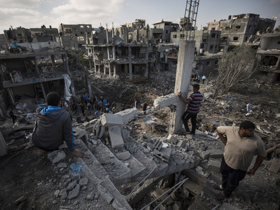 Palestinians inspect their destroyed houses Friday following overnight Israeli airstrikes in Beit Hanoun in the northern Gaza Strip. (Khalil Hamra/AP)