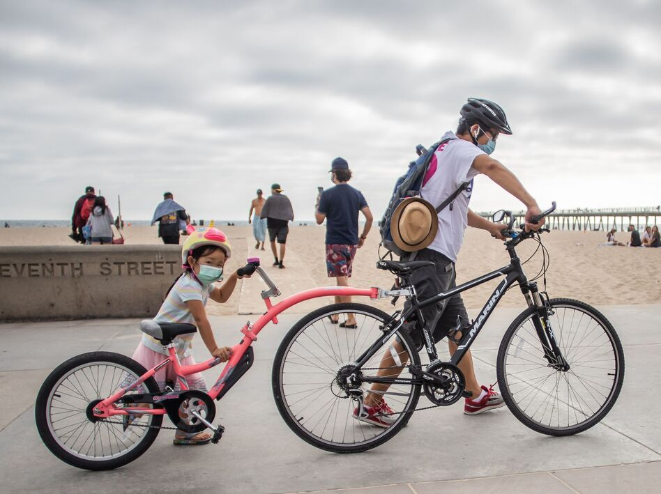 A girl and her father wear face masks while they push their bikes last summer in Hermosa Beach in the Los Angeles area. There aren't yet coronavirus vaccines approved in the U.S. for kids under 12 — which means they should keep masking, according to the CDC.