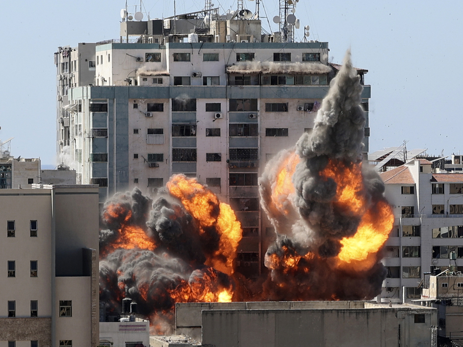 A ball of fire erupts from a building housing various international media, including The Associated Press, after an Israeli airstrike on Saturday in Gaza City. AP staffers and other tenants safely evacuated the building after the Israeli military telephoned a warning that the strike was imminent. (Mahmud Hams/AP)