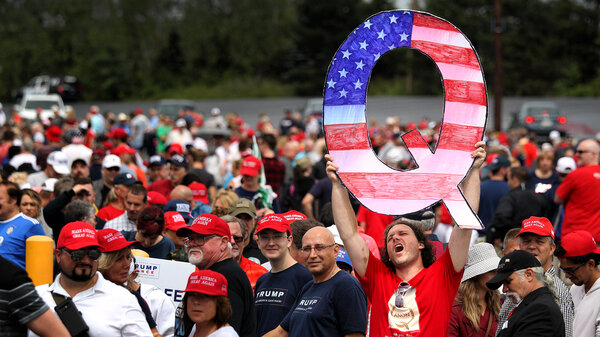 David Reinert holds up a large sign that represents QAnon while waiting in line to see then-President Donald Trump at his rally in Wilkes-Barre, Pa., on Aug. 2, 2018.
