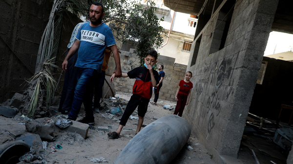 Palestinians look at an unexploded bomb dropped by an Israeli F-16 warplane on Gaza City