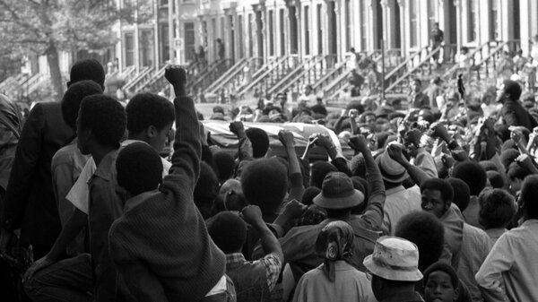 On a Brooklyn street in September 1971, a sea of fists greets the caskets of several of the incarcerated men killed in the violent clash at Attica Correctional Facility that month.