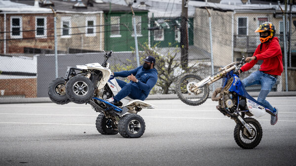 Instructor Harold Toms (left) and participant Tathaiso Martin, 18, ride wheelies in a Baltimore parking lot. B-360, run by founder Brittany Young, is a program that seeks to offer alternatives to recklessly riding dirt bikes and ATVs on city streets.